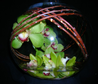 orchids & twigs wrapped inside a glass bowl